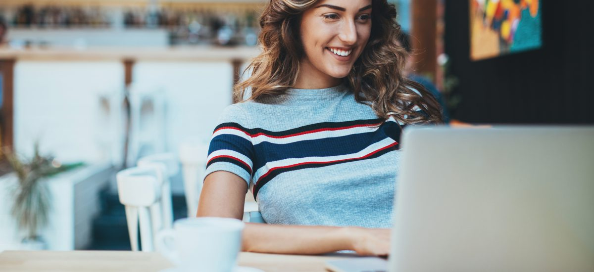 Smiling young woman sitting in cafe holding a coffee cup and working on a laptop.